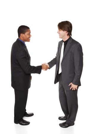 Studio isol� abattu de deux hommes d'affaires se serrant la main dans un cadre chaleureux, accueil amical.