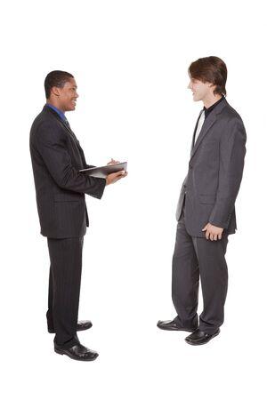 dos personas hablando: Chupito de estudio aisladas de dos empresarios de intercambio de ideas y tomando notas en un cuaderno.