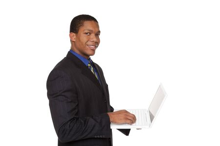 Isolated studio shot of a smiling confident businessman looking at the camera while holding a laptop computer. photo