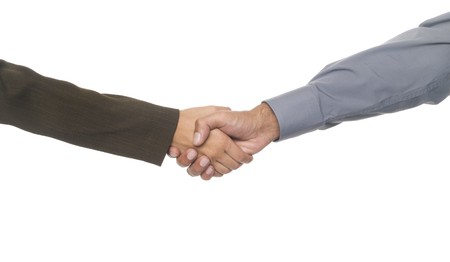 Isolated studio shot of a businessman and businesswoman shaking hands. Фото со стока