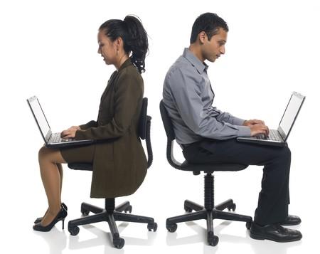 ビジネスマンのスタジオ ショットを分離したラップトップ コンピューターを使用して椅子に座って座っています。