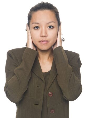 Isolated studio shot of a businesswoman in the Hear No Evil pose. photo