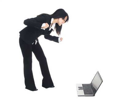 pantsuit: Isolated studio shot of a businesswoman gesturing angrily at a laptop computer on the floor as if she lost a bid.