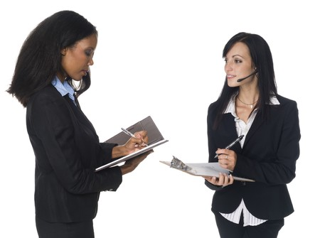 left handed: Isloated studio shot of an African American and Caucasian businesswomen writing on their notepad and clipboard. Stock Photo
