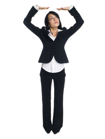 pantsuit: Isolated studio shot of a businesswoman with her arms raised overhead as if she were holding something up. Stock Photo