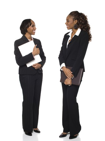 Isolated full length studio shot of two happy businesswomen talking to each other.