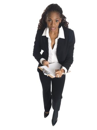 Isolated high angle studio shot of a businesswoman writing on a clipboard. Zdjęcie Seryjne