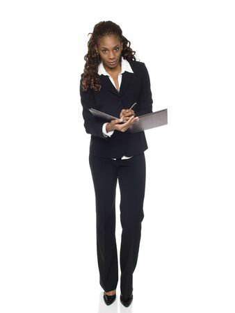 Isolated studio shot of a businesswoman writing on a notepad.
