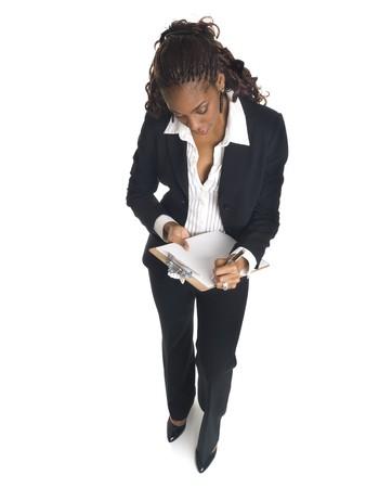 questionaire: Aislado disparo de estudio de alto �ngulo de una empresaria escribiendo en un Portapapeles.  Foto de archivo