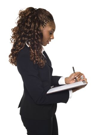 pantsuit: Isolated studio shot of a businesswoman writing on a notepad.