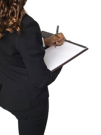 dgf15: Isolated studio shot over the shoulder of a businesswoman writing on a notepad.