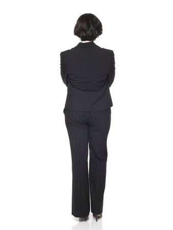 viewed from behind: Isolated studio shot of a businesswoman with her arms crossed viewed from behind.