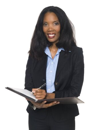 left handed: Isloated full length studio shot of a left handed African American woman looking at the camera and smiling as she writes on her notepad. Stock Photo