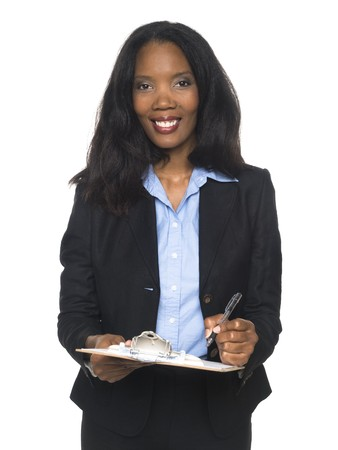 Isloated studio shot of an African American woman looking at the camera while smiling and writing on a clipboard whe is holding.