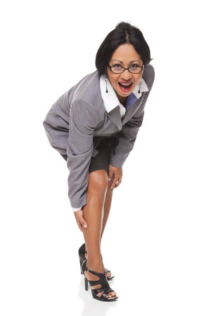 bending over: Isolated studio shot of a Latina businesswoman bending over and clutching her leg while looking at the camera. Stock Photo