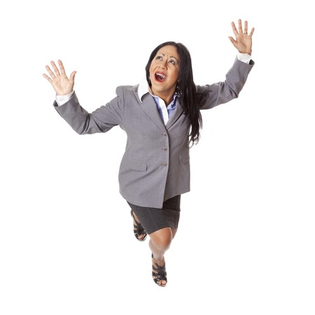 fear: Isolated high angle full length studio shot of a Latina businesswoman looking up in fear with arms raised as if fleeing from a perilous situation.