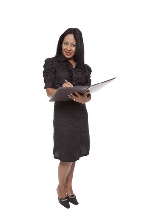Isolated studio shot of a Latina businesswoman taking notes on a notepad while standing. photo
