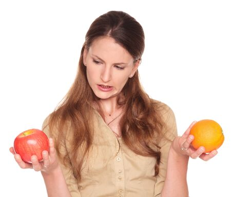 Isolated studio shot of a Caucasian businesswoman comparing an apple to an orange and trying to make a decision.