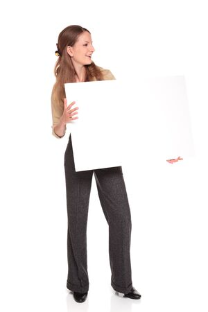 Isolated full length studio shot of a Caucasian businesswoman smiles as she looks over a blank sign.