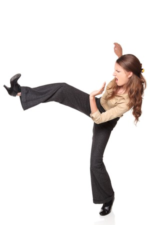Isolated studio shot of a Caucasian businesswoman kicking high up in the air.