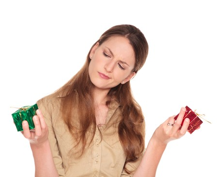 Isolated studio shot of a Caucasian businesswoman comparing red and green Christmas presents and trying to make a decision. Stock Photo