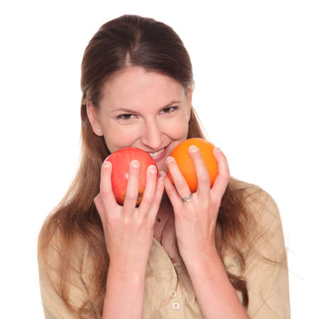 dgf22: Isolated studio shot of a Caucasian businesswoman holding an apple and orange close to her face while trying to choose between them.