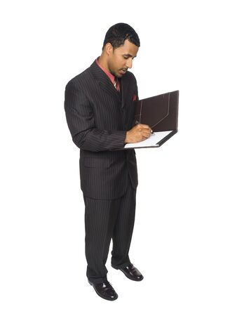 Isloated full length studio shot of an African American businessman writing on a notepad. photo