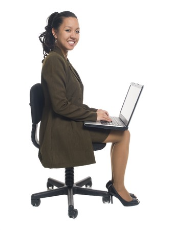 Isolated studio shot of a businesswoman smiling while sitting on an office chair and using her laptop. photo