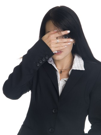 pantsuit: Isolated studio shot of a businesswoman peeking through the hand covering her eyes.