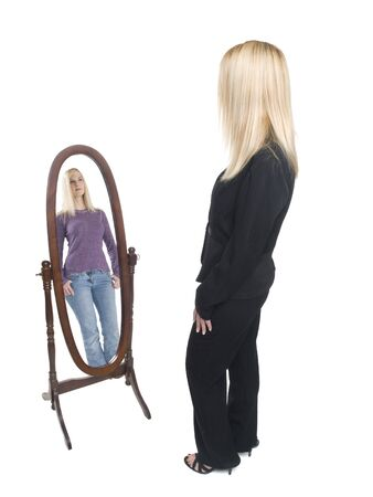 full length mirror: Isolated full length studio shot of a businesswoman looking into a mirror and wishing she had the day off. Stock Photo