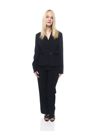 Isolated full length studio shot of a businesswoman looking directly at the camera with a small smile.