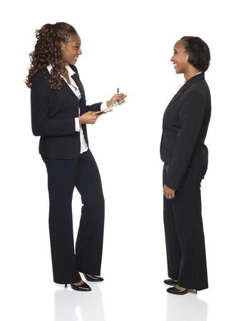 questionaire: Una empresaria escribe las respuestas en un cuestionario o rellena formularios durante una entrevista.