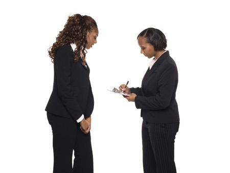 Stock photo of an African American businesswoman answering a questionaire being taken by another businesswoman. Stock Photo