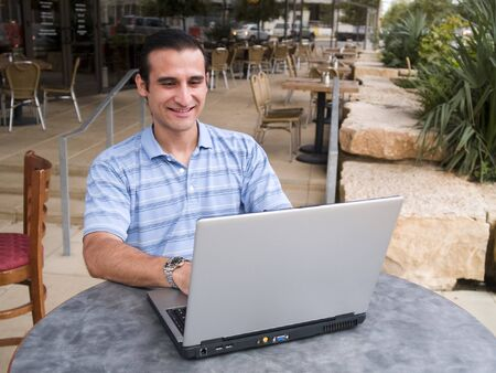 Handsome hispanic male surfing the internet on a laptop and smiling.