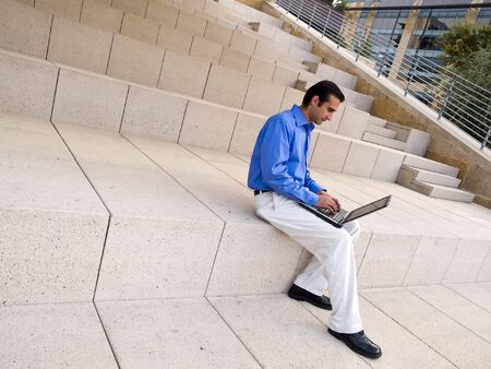 Handsome hispanic businessman surfing the internet on a laptop whle sitting on steps outside an office building. Stock Photo - 8081608