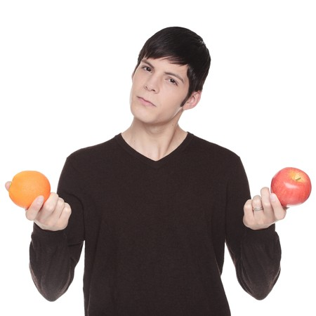 Isolated studio shot of a Caucasian man looking at camera comparing an apple to an orange. photo