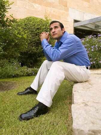 Handsome hispanic businessman sitting on a rock outside an office building.