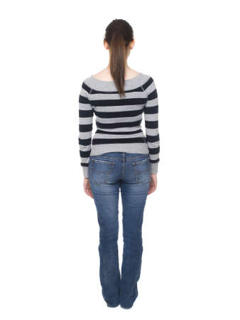 behind: Isolated full length rear view studio shot of a casually dressed young adult woman looking away from the camera. Stock Photo