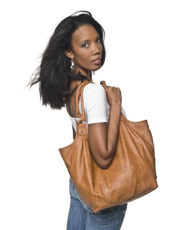 Isolated studio shot of a woman carrying a large handbag and looking over her shoulder.
