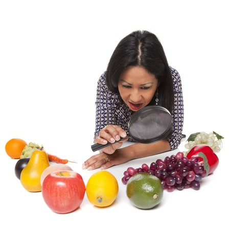 what to eat: Isolated studio shot of a Latina woman examining fruits and vegetables, deciding what to eat for her healthy diet.