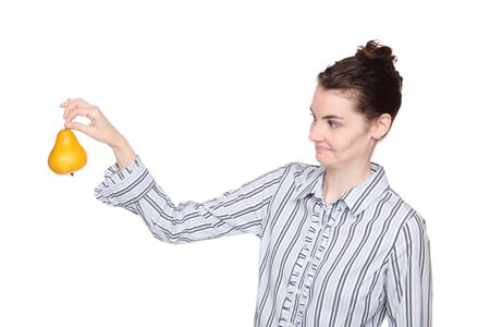 disgusted: Isolated studio shot of a Caucasian woman holding out a pear at arms length with a disgusted expression. Stock Photo