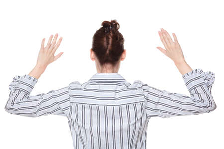 stickup: Isolated studio shot of the rear view of a Caucasian woman holding her hands up in the air as if being robbed.