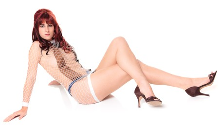 Sexy woman wearing neckties under a fishnet dress sitting and looking at the camera. photo