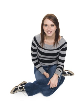 Isolated studio shot of a casually dressed young adult woman sitting on the floor and smiling up at the camera. photo