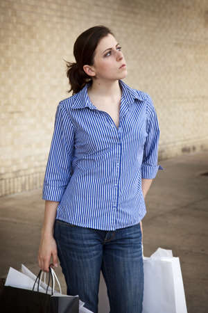 A casually dressed young woman carrying shopping bags and looking away up over the parking lot. photo
