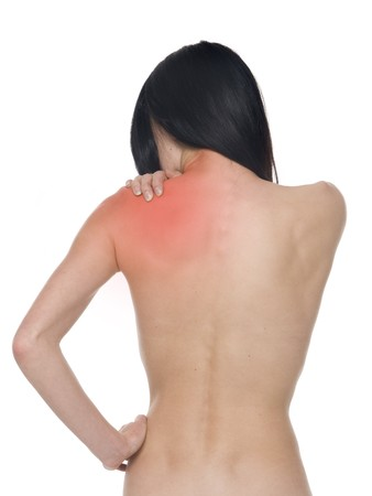 A stressed woman massages her neck to relieve tension.