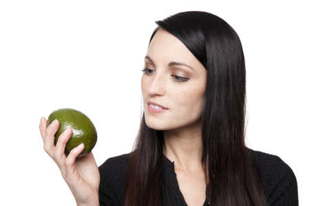 Isolated studio shot of a dark haired caucasian woman looking happily at a vibrant fresh lime. Stock Photo