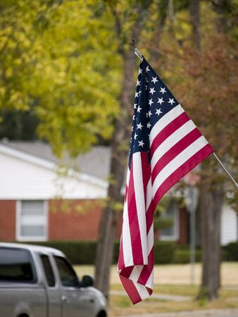 An american flag flying in a suburban neighborhood. Stock Photo - 8046892