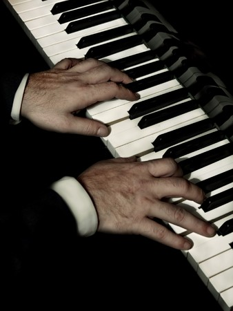 piano player: Stock photo of a closeup of a mans hands playing a piano.
