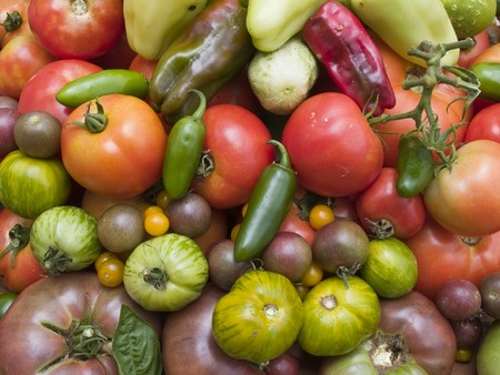 heirloom: A pile of fresh organically grown vegetables, including tomatoes, jalepenos, banana peppers, sweet red peppers, and heirloom tomatoes.
